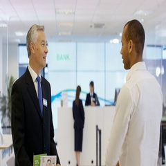 4K Customers wait to meet with financial adviser in modern bank Stock Footage