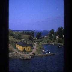 1975: a house next to a clear, blue lake at daytime, seen from above SWEDEN Stock Footage