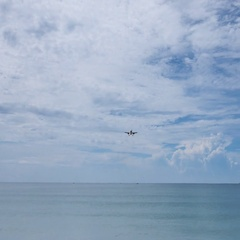 Commercial plane flying over the sea coming to camera and landing Stock Footage