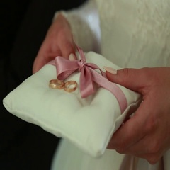 Wedding rings for the newlyweds in the hands on silk pillow Stock Footage