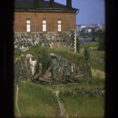 1975: a rustic old brick and stone building atop a green hill SWEDEN Stock Footage