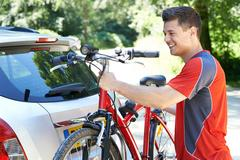 Male Cyclist Taking Mountain Bike From Rack On Car Stock Photos