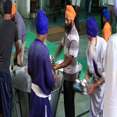 Poor people clean dishes at soup kitchen in Sikh Golden Temple, Amritsar, India Stock Footage