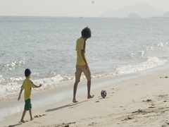 Boy with Man playing football at the beach. Stock Footage