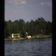 1976: view of large house on the coast as seen from a passing marine vessel. Stock Footage
