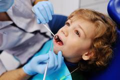 Cute baby in a striped sweater on reception at the dentist Stock Photos