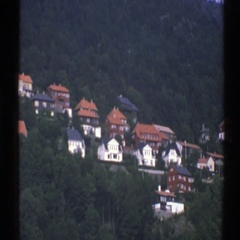 1976: vegetation on a hill along with many residential structures in a city  Stock Footage
