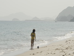 Man playing football with boy at the beach. Stock Footage
