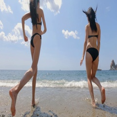Two slender brunettes with long hair in black bikinis running into the sea Stock Footage