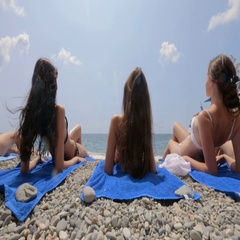 Attractive young women in bikinis sunbathing on the beach Stock Footage