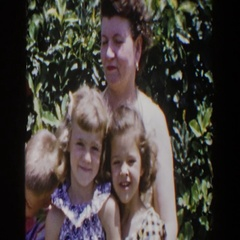 1953: a mum sitting outdoors on a windy day with three children LUBBOCK TEXAS Stock Footage