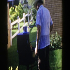 1953: man grilling on a sunny day in the backyard of his home LUBBOCK TEXAS Stock Footage