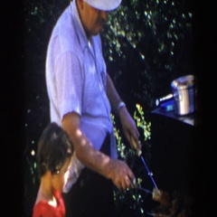 1953: man grilling while child watches LUBBOCK TEXAS Stock Footage