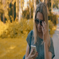 Woman goes park with her phone at summer day under sun light Stock Footage