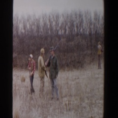 1956: four hunters are wading through the tall dry grass on a cloudy day LUBBOCK Stock Footage