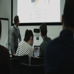 Professor teaching with projector synced to students digital tablets Stock Footage