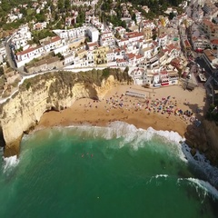 Aerial. Shoot waves over the beach village of Carvoeiro. Portugal. Stock Footage