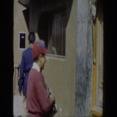 1951: boy wearing cap and holding shoe-shine kit turns around twice on sidewalk Stock Footage