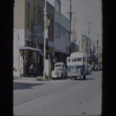 1951: a street with several parked cars along the curb with buses and cars Stock Footage