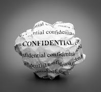 Crumpled paper ball with words Confidential on gray background. Stock Photos
