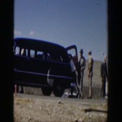 1951: men standing out by a car wreck, working on their own vehicle. TEXAS Stock Footage