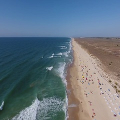 Aerial. Flying over Barril beach with tourists, from the sky in the summer. Stock Footage