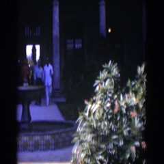 1951: people walking out from a very fancy hotel and a lady sitting out front. Stock Footage