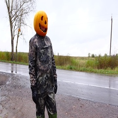 Jack Pumpkinhead stand at empty road side, put arms on waist, half length Stock Footage