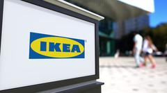 Street signage board with Ikea logo. Blurred office center and walking people Stock Illustration