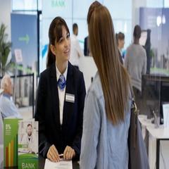 4K Portrait smiling bank worker on information desk  Stock Footage