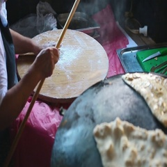 Granny chef cook Turkish pancake Gozleme on the stove Stock Footage