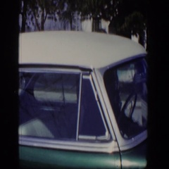 1954: a person is sitting inside a green and white colored sedan parked  Stock Footage