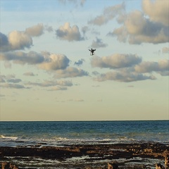 Drone flying in the blue cloudy sky over the sea coast. Sunset. Camera follows t Stock Footage