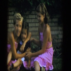 1954: 3 little girls, 2 in matching pink halter skirt outfits, sit and wave  Stock Footage