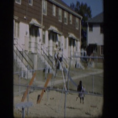 1954: two girls go down a slide while a third girl is on a swing  Stock Footage