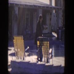 1954: woman in a coat walking along a public pool. NEVADA Stock Footage