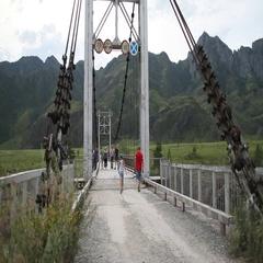 Bridge over mountain river. Girl. Russian Siberia. Altai. The mountains. Stock Footage