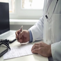 Doctor sitting by the table and writing documents Stock Footage