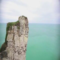 Lonely rocky cliff above endless blue sea, flying birds, serene landscape Stock Footage