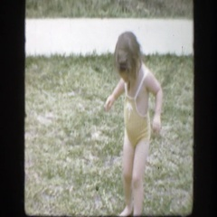 1945: a child walking outside in a yellow bathing suit with no shoes FLORIDA Stock Footage