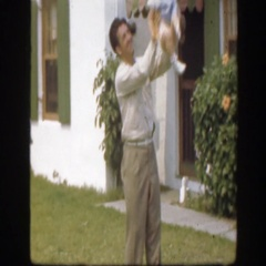 1945: daddy throws his thrilled baby girl in the air and catches her  Stock Footage