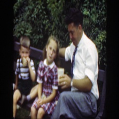 1948: dad with young girl and boy on a park bench eating and drinking WASHINGTON Stock Footage