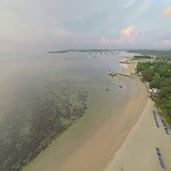 Aerial shot of sunrise in Sanur beach, camera panning left on the shallow water Stock Footage