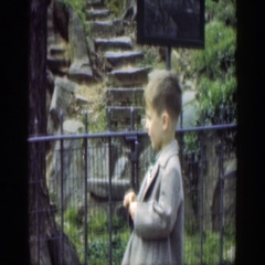 1949: cute child standing wearing jacket in a garden area CINCINNATTI OHIO Stock Footage