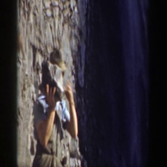 1937: a man wearing a hat and throwing a large rock into a waterfall CALIFORNIA Stock Footage