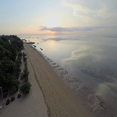 Aerial shot of sunrise in Sanur beach, camera descending on the beach Stock Footage