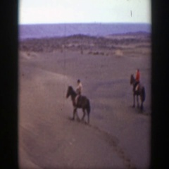 1939: three individuals horseback riding on desert terrain MONTANA Stock Footage