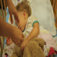 The sweet baby sleeps in a cot with a teddy bear. mother moves a teddy bear Stock Footage