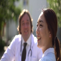 Profiled smiling Asian nurse talking outdoors with a male doctor Stock Footage