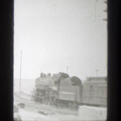 1939: passenger train passes through swiftly, with low hills in background Stock Footage